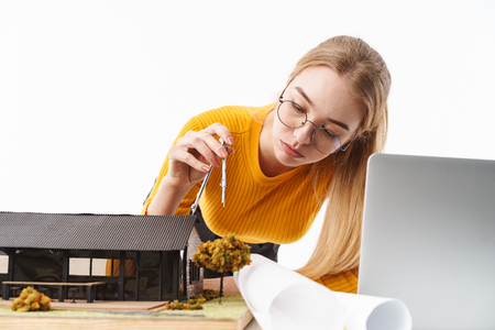 Beautiful young blonde woman architect standing isolated over white background, working on a new project at the desk with laptop