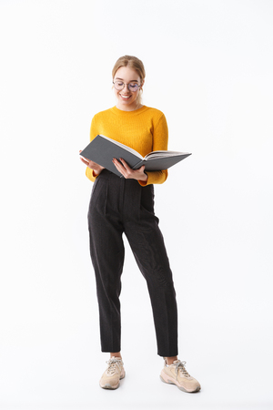 Full length of a smiling attractive young blonde woman wearing sweater standing isolated over white background, holding opened book 스톡 콘텐츠