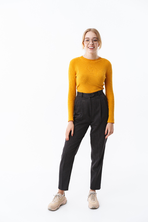 Full length of a smiling attractive young blonde woman wearing sweater standing isolated over white background Stock Photo