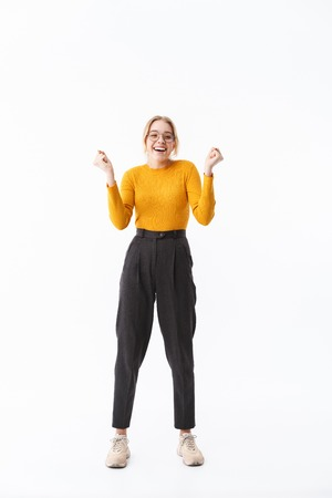 Full length of a smiling attractive young blonde woman wearing sweater standing isolated over white background, celebrating success