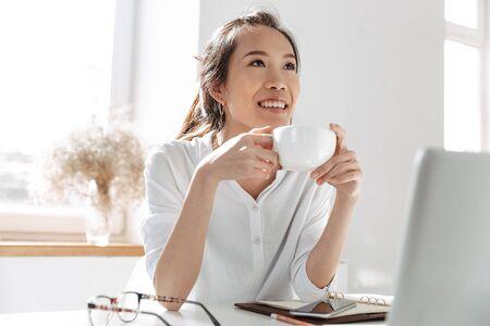Peinzende glimlachende aziatische zakenvrouw die koffie drinkt en wegkijkt terwijl ze bij de tafel op kantoor zit