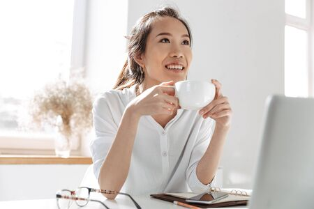 Pensive smiling asian business woman drinking coffee and looking away while sitting by the table in office Imagens