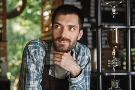 Image of excited barista boy wearing apron making coffee while working in cafe or coffeehouse outdoor Stock Photo
