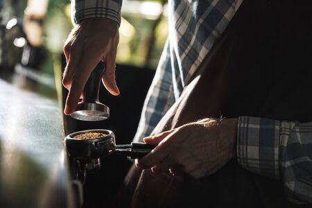 Image closeup of masculine barista man wearing apron making coffee while working in cafe or coffeehouse outdoor
