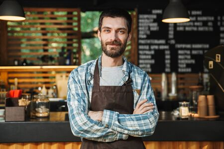Portrait of caucasian barista guy wearing apron smiling and standing with arms crossed in street cafe or coffeehouse outdoor Stock Photo