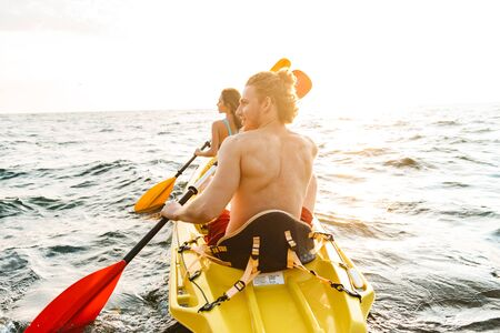 Back view of a sporty attractive couple kayaking on sea together
