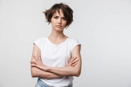 Portrait of serious woman with short brown hair in basic t-shirt frowning and looking at camera isolated over white background Banco de Imagens - 125235027