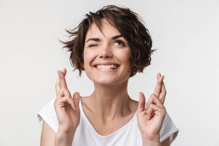 Portrait of brunette woman with short hair in basic t-shirt keeping fingers crossed and wishing good fortune isolated over white background