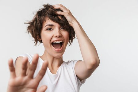 Image of a beautiful young pretty excited happy woman posing isolated over white wall background laughing.