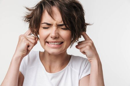 Image of a beautiful young pretty displeased stressed woman posing isolated over white wall background covering ears because of loud.
