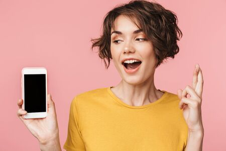 Image of a young beautiful woman posing isolated over pink wall background using mobile phone showing display and hopeful please gesture.