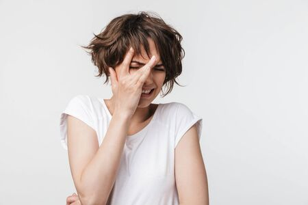Portrait of scared woman with short brown hair in basic t-shirt frowning and covering her eyes isolated over white background