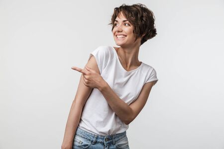 Portrait of happy woman with short hair in basic t-shirt rejoicing and pointing finger at copyspace isolated over white background
