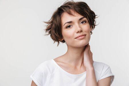 Portret van een mooie vrouw met kort bruin haar in een basic t-shirt die naar de camera kijkt terwijl ze geïsoleerd staat op een witte achtergrond