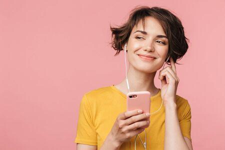 Imagen de una mujer hermosa joven feliz posando aislada sobre fondo de pared rosa escuchando música con auriculares mediante teléfono móvil.