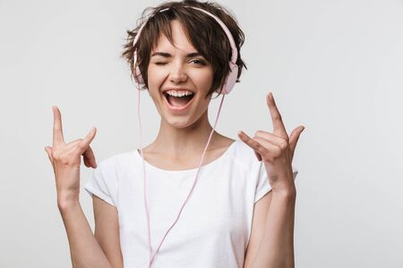 Image of joyous woman in basic t-shirt showing rock sign while listening to music with headphones isolated over white background