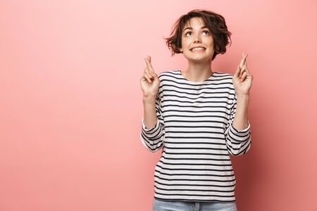 Image of young emotional beautiful woman posing isolated over pink wall background make hopeful please gesture.