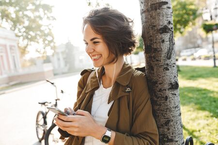 Picture of a cute young pretty woman walking outdoors in park in beautiful spring day using mobile phone.