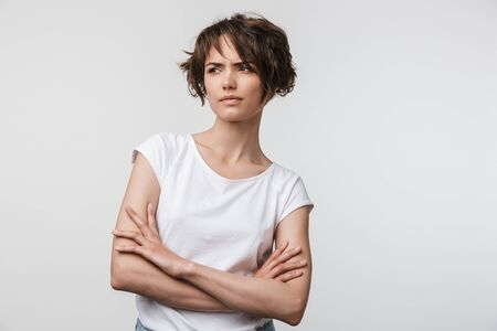 Portrait of angry woman with short brown hair in basic t-shirt frowning and looking at camera isolated over white background Banco de Imagens