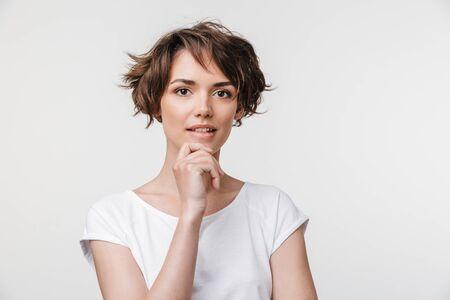 Porträt einer attraktiven Frau mit kurzen braunen Haaren in einem einfachen T-Shirt, die im Stehen isoliert auf weißem Hintergrund in die Kamera schaut Standard-Bild