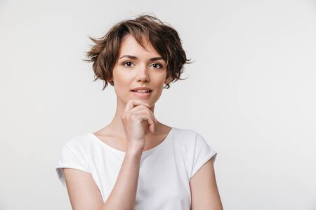Portrait of attractive woman with short brown hair in basic t-shirt looking at camera while standing isolated over white background
