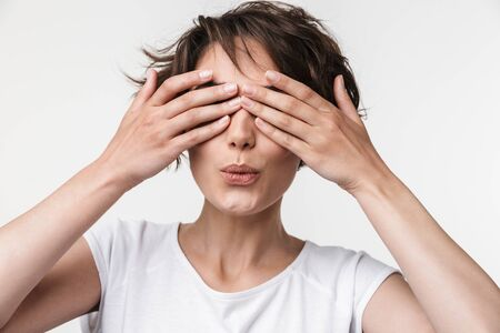 Portrait of european woman with short brown hair in basic t-shirt covering her eyes with hands isolated over white background