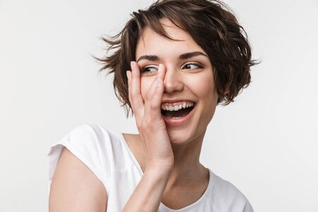 Portrait of happy woman with short brown hair in basic t-shirt smiling and touching her face with hand isolated over white background