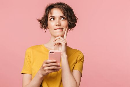 Image of a thinking dreaming young beautiful woman posing isolated over pink wall background using mobile phone.