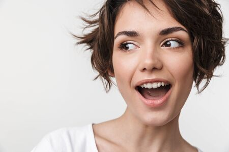 Portrait closeup of cheery woman with short brown hair in basic t-shirt smiling at camera isolated over white background Фото со стока
