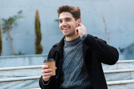 Image of happy man 30s wearing earpods smiling and drinking takeaway coffee while sitting on city stairs