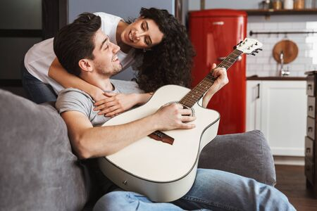 Image of caucasian young couple man and woman 30s sitting on sofa at home and playing music on acoustic guitar