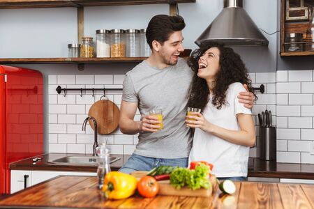 Portrait of optimistic couple man and woman 30s cooking salat with vegetables together while having breakfast in kitchen at home Banque d'images - 125044806