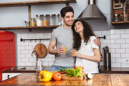 Portrait of adorable couple man and woman 30s cooking salat with vegetables together while having breakfast in kitchen at home Banque d'images - 125044815