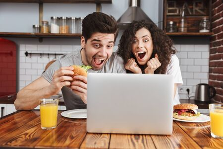 Picture of caucasian couple man and woman 30s looking at laptop on table while eating hamburger in kitchen at home Banque d'images - 125044752