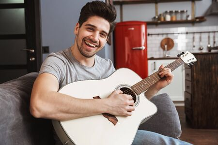 Image of smiling handsome man 30s sitting on sofa at home and playing music on acoustic guitar
