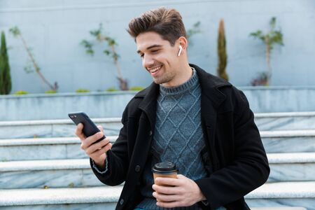 Image of happy man 30s wearing earpods holding smartphone and drinking takeaway coffee while sitting on city stairs