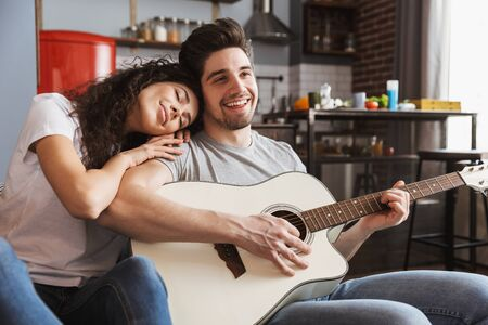 Image of happy young couple man and woman 30s sitting on sofa at home and playing music on acoustic guitar