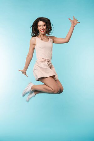 Full length of a cheerful young brunette woman jumping isolated over blue backgorund