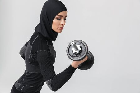 Image of young woman fitness muslim posing isolated over white wall background make exercises with dumbbell.