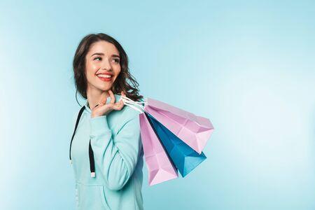 Portret van een mooie opgewonden jonge brunette vrouw die geïsoleerd staat over een blauwe achtergrond en boodschappentassen draagt Stockfoto