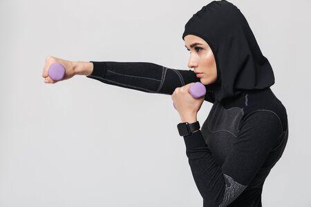 Imagen del boxeador de combate musulmán de fitness mujer joven posando aislado sobre fondo de pared blanca hacer ejercicios con pesas.