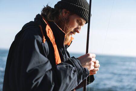 Image d'un beau jeune pêcheur concentré portant un manteau et un chapeau au bord de la mer. Banque d'images