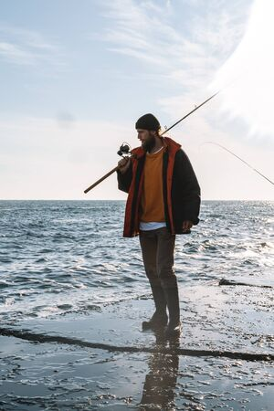 Image of a handsome concentrated young man fisherman wearing coat and hat at the seashore.