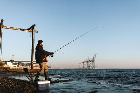 Silhouette of man fisherman wearing coat, holding rod, fishing at the beach