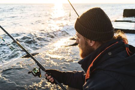 Handsome brutal bearded fisherman wearing coat sitting with a fishing rod at the seashore