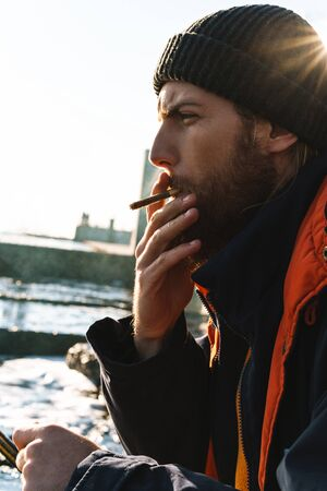 Picture of a handsome young man fisherman wearing coat and hat at the seashore smoking.