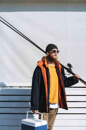 Handsome brutal bearded fisherman wearing coat standing with a fishing rod at the seashore