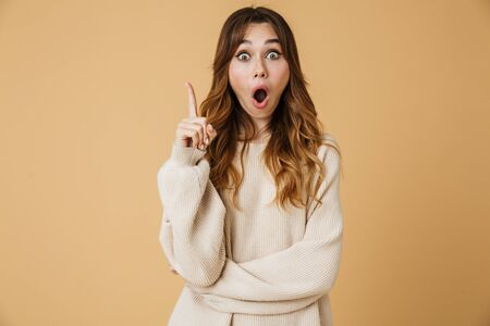 Beautiful young woman wearing sweater standing isolated over beige background, presenting copy space Stock Photo