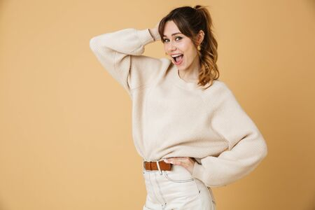 Beautiful young woman wearing sweater standing isolated over beige background, posing