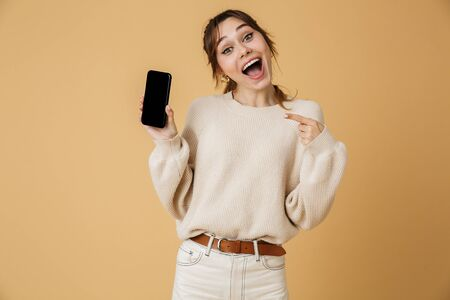 Beautiful cheerful young woman wearing sweater standing isolated over beige background, presenting blank screen mobile phone Reklamní fotografie